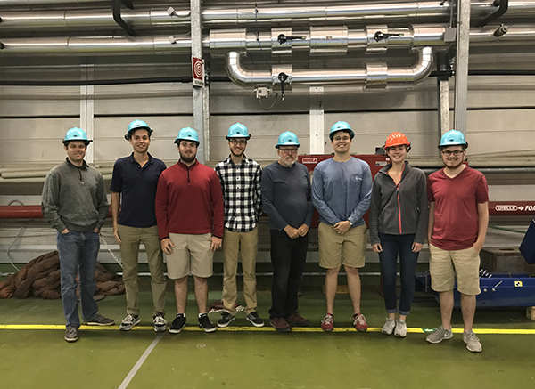 group of students and Dr. Landsberger wearing hard hats