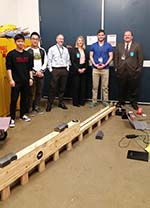 Senior Design class students with professors standing by project