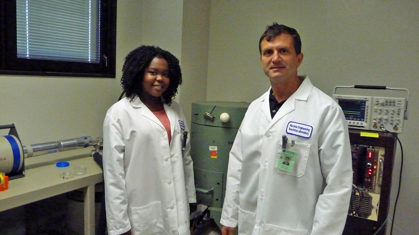 student and professor in lab coats in lab