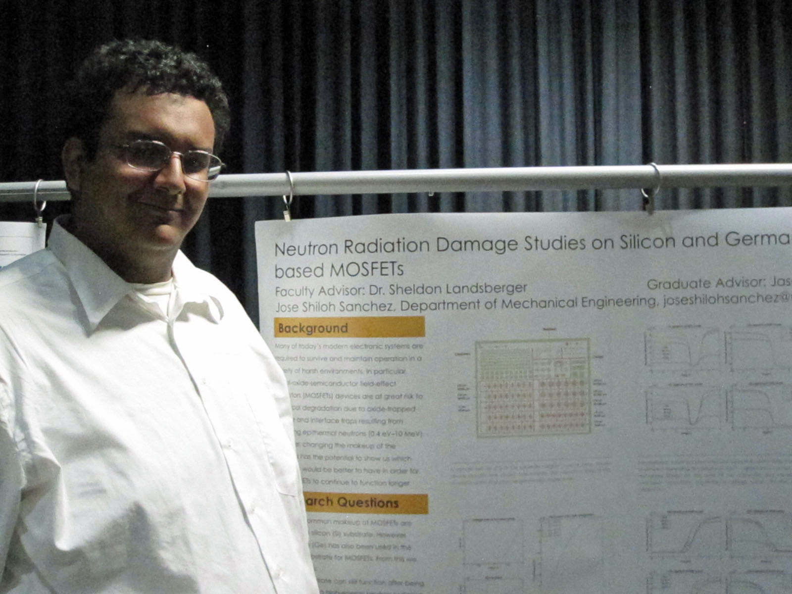 student standing in front of poster presentation