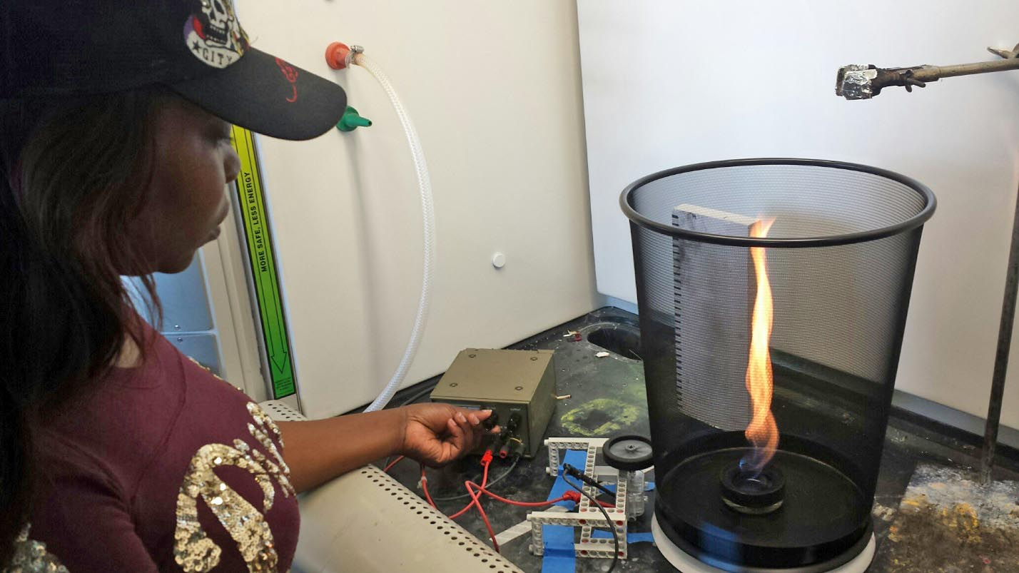 student adjusting flame in experiment